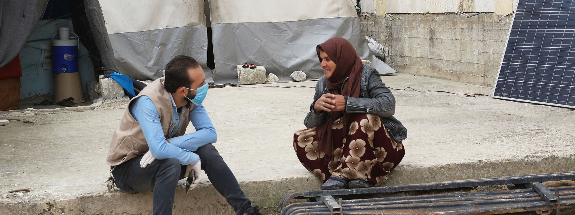 A ReliefAid worker wearing face mask and gloves talks to a woman during assessments at a camp in Idlib, Syria