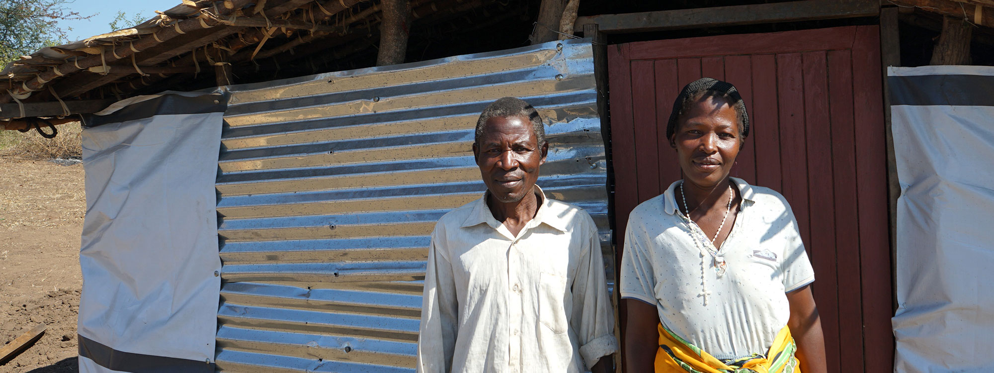 couple outside their home in malawi