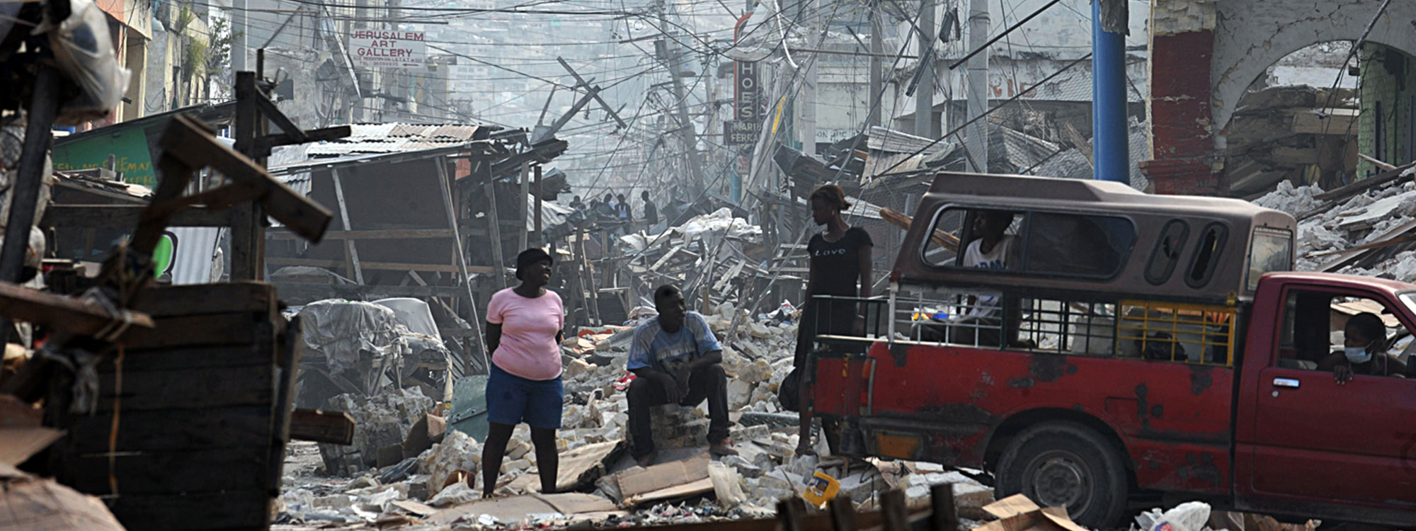 people standing amongst destroyed buildings after haiti earthquake