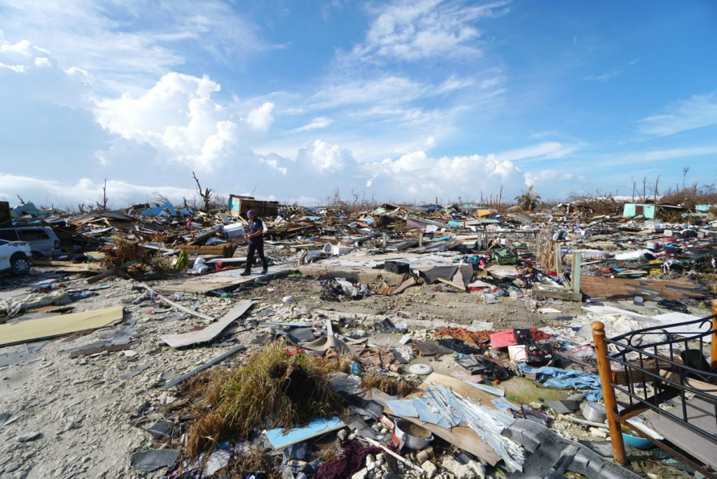 A bed frame and piles of other debris scattered across the Bahamian landscape after Hurricane Dorian
