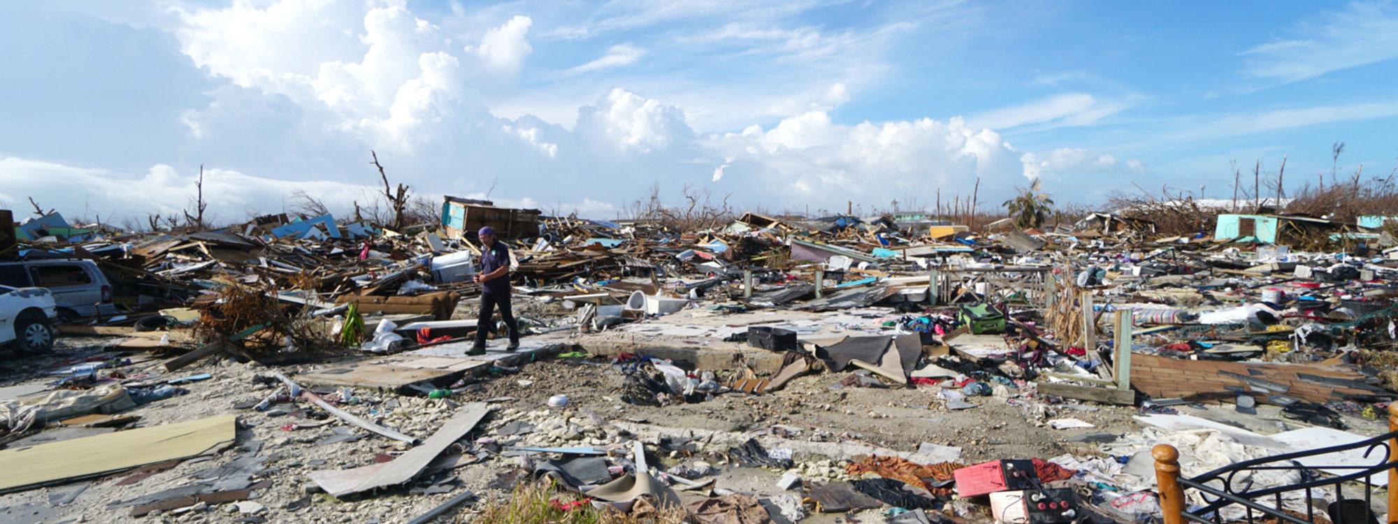 Man walks amongst widespread destruction in the Bahamas in 2019, following hurricane Dorian