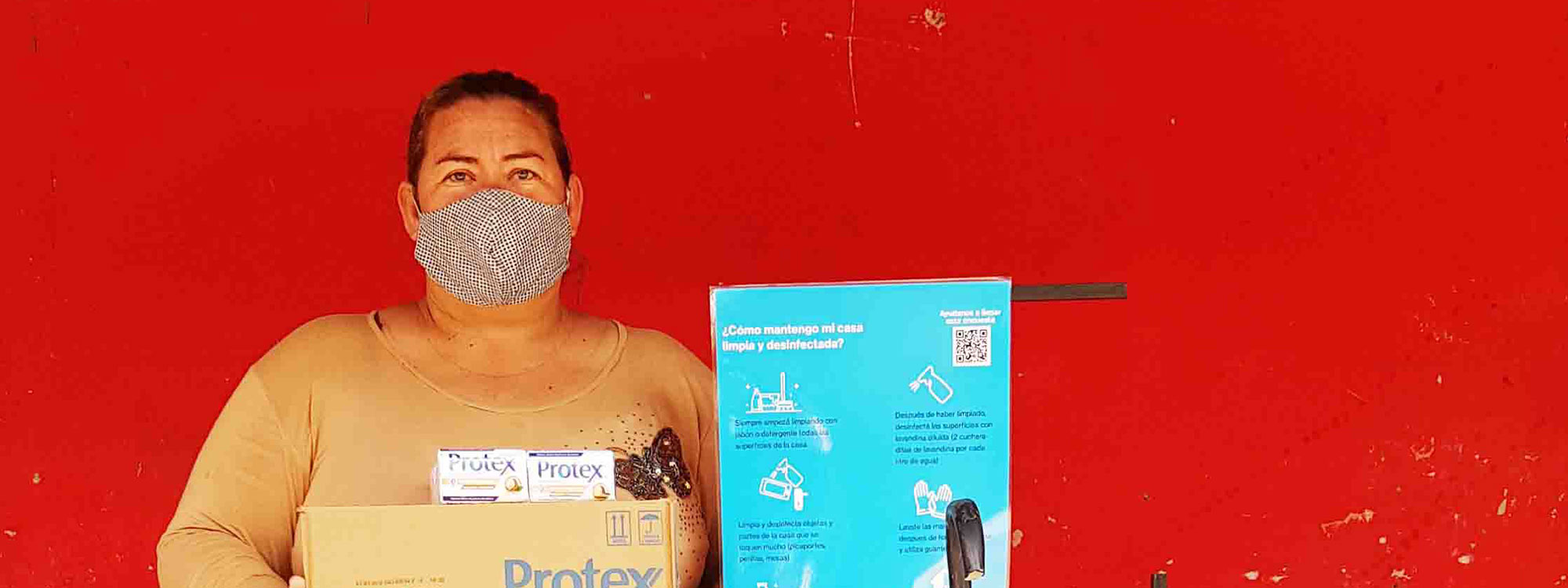 woman stands next to infomational signs about coronavirus in paraguay