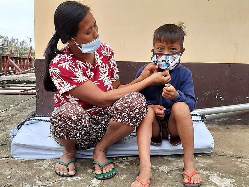 Young boy with his mask being fixed by his mother