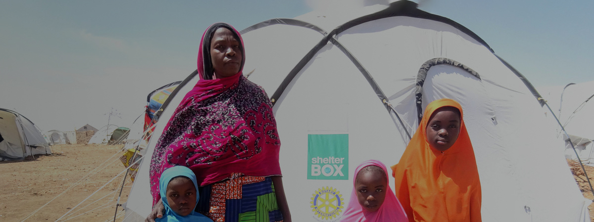A woman standing in front of a tent with three children around her