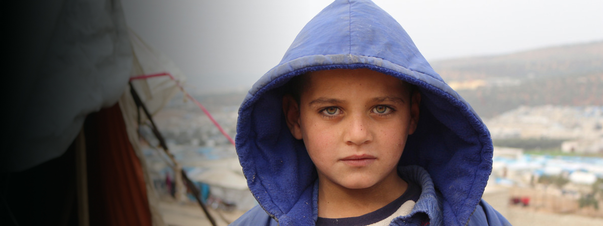 Boy with green eyes wearing a purple hooded coat
