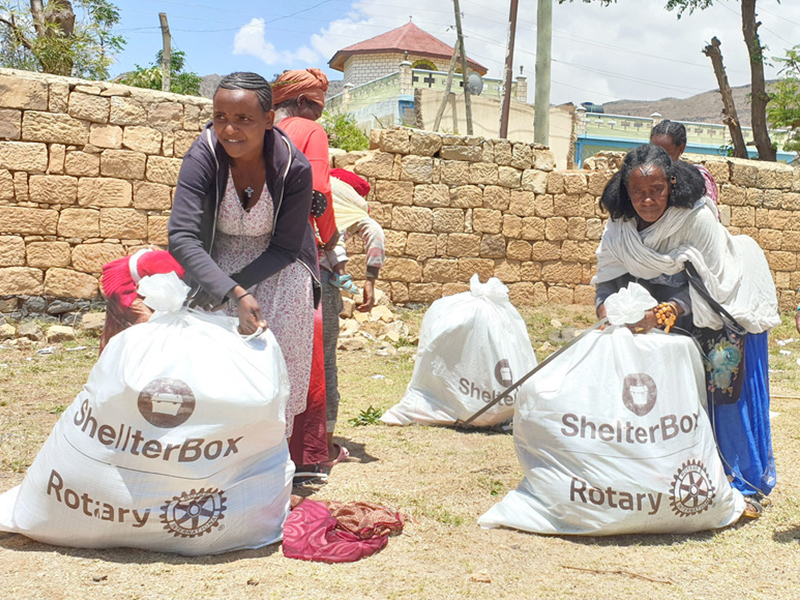 people holding bags with aid
